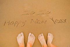 Liebhaber schreiben 2020 guten Rutsch ins Neue Jahr auf Strand Stockfoto