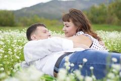 Liebhaber treffen Männer und Frauen auf einem schönen Blumenfeld lizenzfreie stockfotos