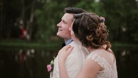 Liebhaberanteil Intimatemoment Junge Frau umarmt ihren Mann, der hinter ihm steht und küsst ihn auf einer Backe Mann schließt Aug stock footage