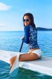 liebhaberei Mädchen, das auf Surfbrett schaufelt Junge Frau auf dem Strand von Formentera-Insel stockfotos