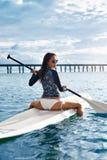 liebhaberei Mädchen, das auf Surfbrett schaufelt Junge Frau auf dem Strand von Formentera-Insel lizenzfreie stockbilder