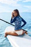 liebhaberei Mädchen, das auf Surfbrett schaufelt Junge Frau auf dem Strand von Formentera-Insel Entspannendes W lizenzfreie stockfotos