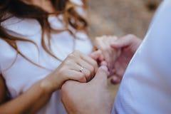 Liebhaberhändchenhalten mit Goldeheringen Braut und Bräutigam Stockfotos