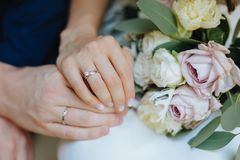 Liebhaberhändchenhalten mit Goldeheringen Braut und Bräutigam Stockfotografie