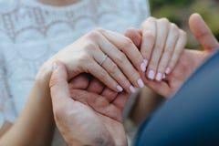 Liebhaberhändchenhalten mit Goldeheringen hochzeit Stockfoto