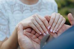 Liebhaberhändchenhalten mit Goldeheringen hochzeit Lizenzfreie Stockbilder