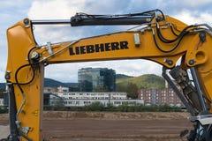 Liebherr水力挖掘机和现代大厦构筑的建造场所武装 海得尔堡,德国- 2017年10月3日 免版税图库摄影