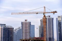 Free LIEBHERR Tower Crane Constructing A New Residential Building At A Construction Site Against Blue Royalty Free Stock Photos - 179527698