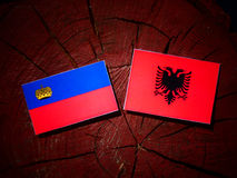 Liechtenstein flag with Albanian flag on a tree stump isolated royalty free illustration