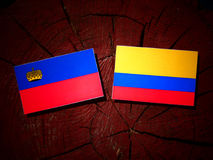Liechtenstein flag with Colombian flag on a tree stump isolated stock illustration