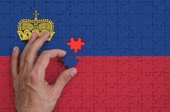 Liechtenstein flag is depicted on a puzzle, which the man`s hand completes to fold.  vector illustration