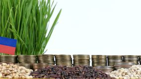 Liechtenstein flag waving with stack of money coins and piles of wheat. And rice seeds stock footage