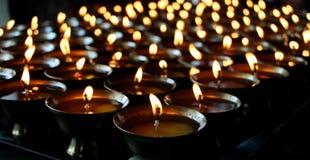 liefdadigheid Het bidden kaarsen in een klooster in Bhutan stock afbeelding
