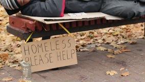 Liefdadigheid, vriendelijke mens die pak van geld op bank verlaten terwijl dakloze mannelijke slaap stock video