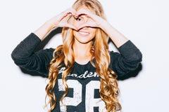 Liefde Close-upportret die gelukkige jonge vrouw met lang blon haar glimlachen, die hart maken ondertekenen, symbool met achtergr Stock Afbeelding