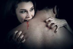 Liefde en bloed - vampiervrouw die haar minnaar bijt stock afbeeldingen