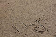 Liefde en hart in het strandzand Stock Foto