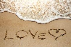 Liefde en hart op het zandstrand dichtbij overzees - conceptueel beeld stock afbeelding