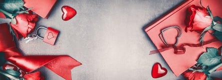 Liefde en van de Valentijnskaartendag concept Mooie rode rozen, die toebehoren, harten, boek, slot en sleutels op grijze bureauac Stock Afbeelding