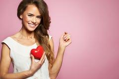 Liefde en van de valentijnskaartendag het hart van de vrouwenholding leuk glimlachen en aanbiddelijk geïsoleerd op roze achtergro Stock Foto's