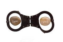 Liefde en Vreugdekiezelstenen in hand manchetten op wit worden geïsoleerd dat Stock Afbeelding