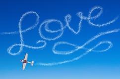 Liefde figuurlijke inschrijving van een wit vliegtuig van de rooksleep Stock Foto