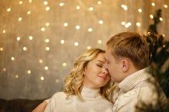 Liefde jonge gelukkige familie, paar het kussen, die dichtbij de Kerstboom in de ruimte zitten Gelukkige Nieuwjaar en Kerstmis Royalty-vrije Stock Foto