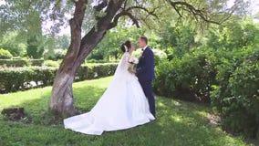 In liefde loopt een jong huwelijkspaar in het park Een echtgenoot met zijn vrouw in witte bruid draagt een gang in aard stock footage