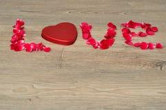 Liefde met rode roze bloemblaadjes en een tin dat van de hartvorm wordt gespeld Stock Afbeeldingen