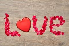 Liefde met rode roze bloemblaadjes en een tin dat van de hartvorm wordt gespeld Stock Foto's
