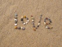 Liefde met stenen die en shells wordt geschreven Stock Foto