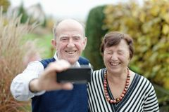 Liefde in nadruk Het gelukkige hogere paar plakken aan elkaar en het maken selfie Stock Foto
