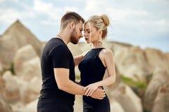 In liefde Oostelijk paar in bergen van de omhelzingen en de kussen van Cappadocia Liefde en emoties die paar van het vacationing  stock afbeelding