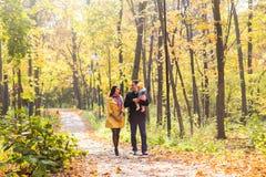 Liefde, ouderschap, familie, seizoen en mensenconcept - glimlachend paar met baby in de herfstpark stock afbeeldingen