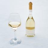 Liefde, Romaans, de wintervakantie, het concept van de Nieuwjaarviering Fles en glas witte die wijn door sneeuw wordt gekoeld Royalty-vrije Stock Fotografie