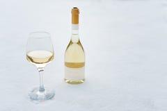 Liefde, Romaans, de wintervakantie, het concept van de Nieuwjaarviering Fles en glas witte die wijn door sneeuw wordt gekoeld Stock Foto's