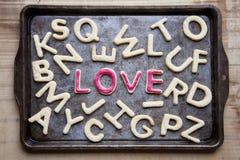 Liefde in rood suikerglazuur onder brief gevormde koekjes Stock Afbeeldingen