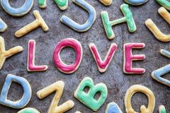 Liefde in rood suikerglazuur onder brief gevormde koekjes, close-up Stock Foto