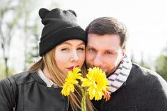 Liefde, verhoudings, familie en mensenconcept - koppel aan boeket van gerberas in de herfstpark stock afbeelding