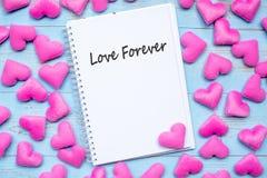 LIEFDE VOOR ALTIJD woord op notitieboekje met de roze decoratie van de hartvorm op blauwe houten lijstachtergrond Huwelijk, Roman royalty-vrije stock fotografie
