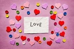 Liefde - woord met kleurrijk harten en decor op roze, valentijnskaartendag of godsdienstconcept stock afbeeldingen