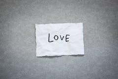 Liefde - woord op Witboek met grijze achtergrond stock foto's