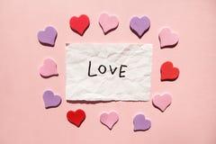 Liefde - woord op Witboek met harten op roze achtergrond, valentijnskaartendag royalty-vrije stock fotografie