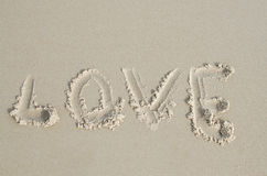 Liefde in zacht nat zand op een strand wordt geschreven dat Royalty-vrije Stock Foto