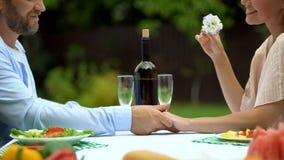 Liefdebekentenis die van de mens op middelbare leeftijd op romantisch diner met vrouw, hand houden stock foto's