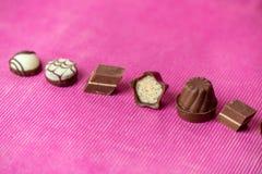 Liefdechocolade - zoete chocolade op een roze achtergrond stock foto