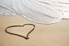 Liefdeconcept - één hart dat op het strandzand wordt getrokken Stock Foto