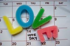 Liefdedag - spons brieven af creërend liefdewoord over witte kalender merkend 14 februari-liefdedag stock fotografie