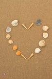 Liefdehart dat van shells op strand wordt gemaakt Royalty-vrije Stock Afbeeldingen