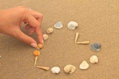 Liefdehart van shells op strand wordt gemaakt dat Stock Afbeeldingen